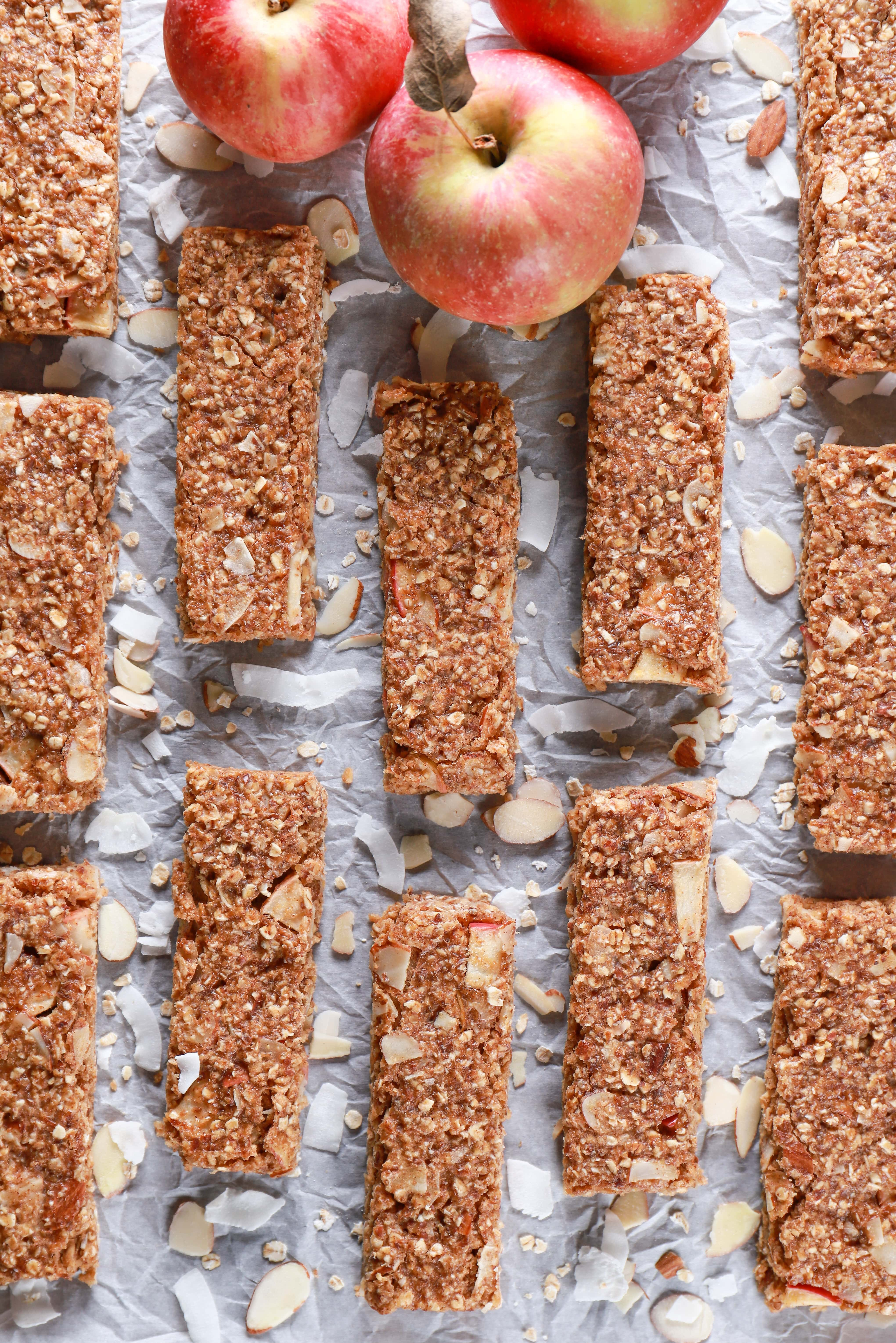 Overhead view of soft baked apple almond granola bars on parchment paper. Recipe from A Kitchen Addiction