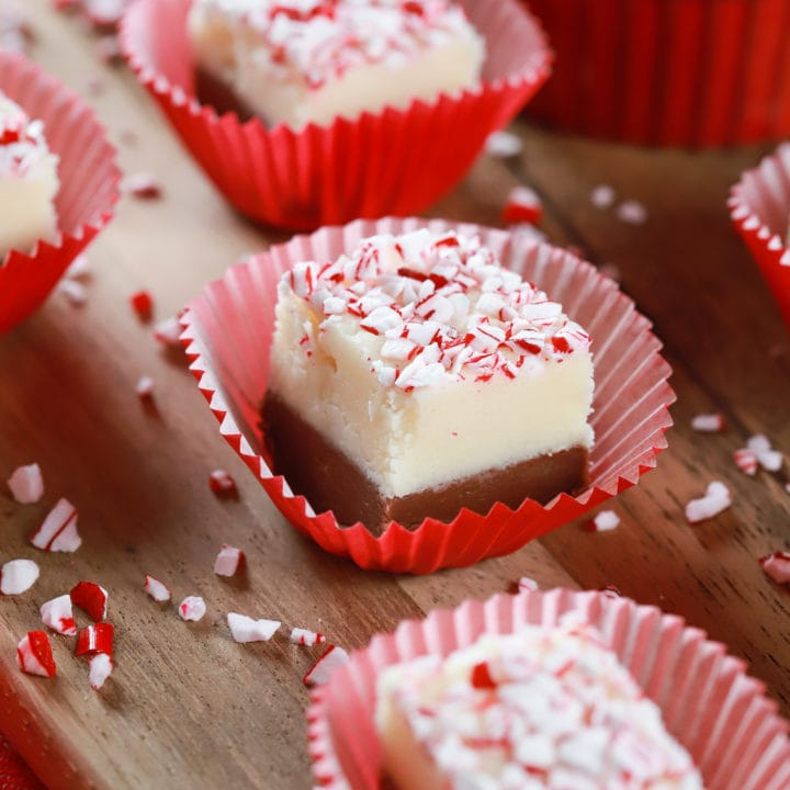 Up close image of a piece of chocolate peppermint layered fudge in a red cupcake liner on a wooden cutting board. Recipe from A Kitchen Addiction