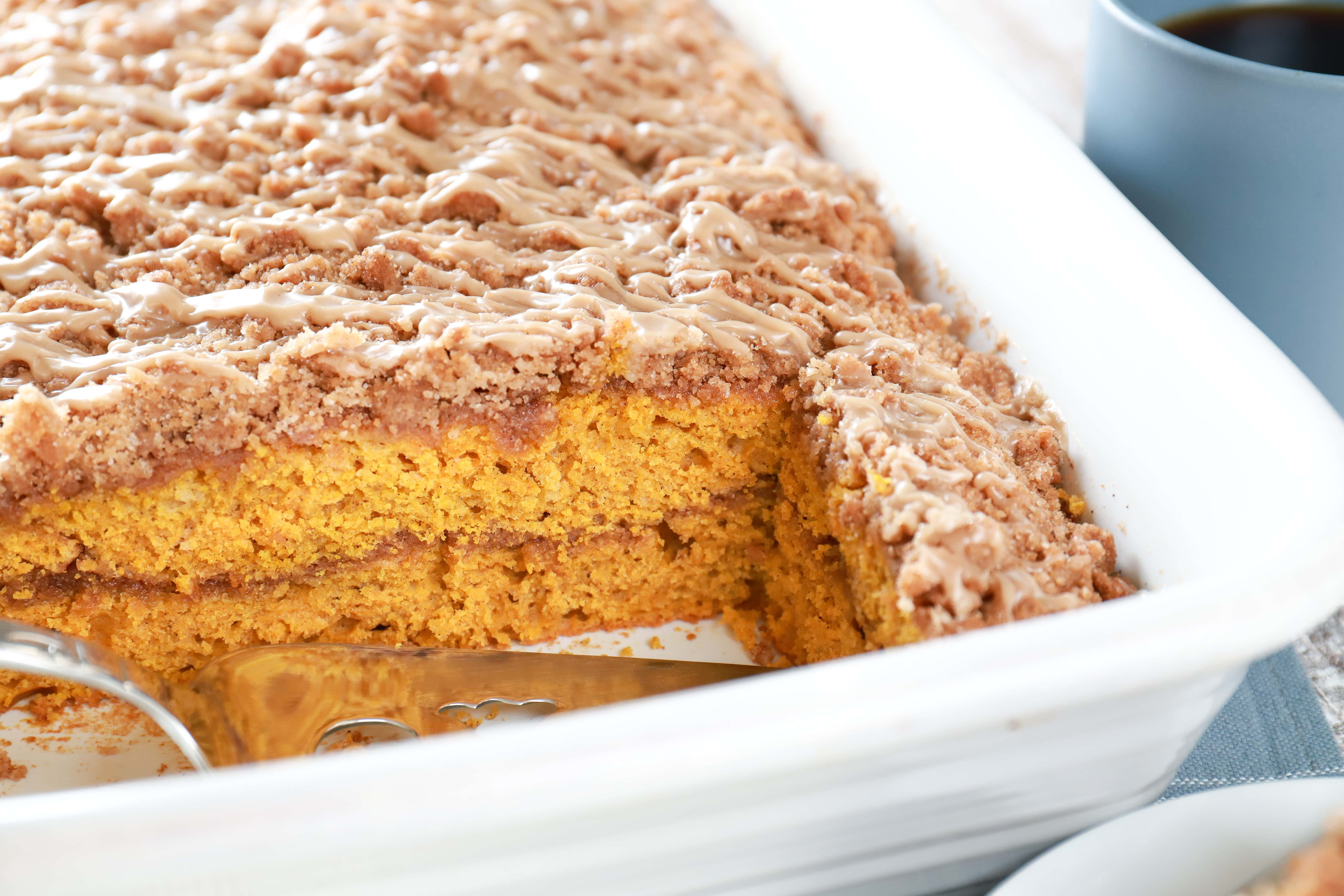Image of row of maple cinnamon pumpkin coffee cake in cake pan. Recipe from A Kitchen Addiction