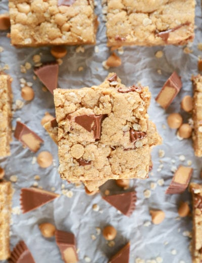 Overhead view of a stack of Peanut Butter Overload Cookie Bars on parchment paper.