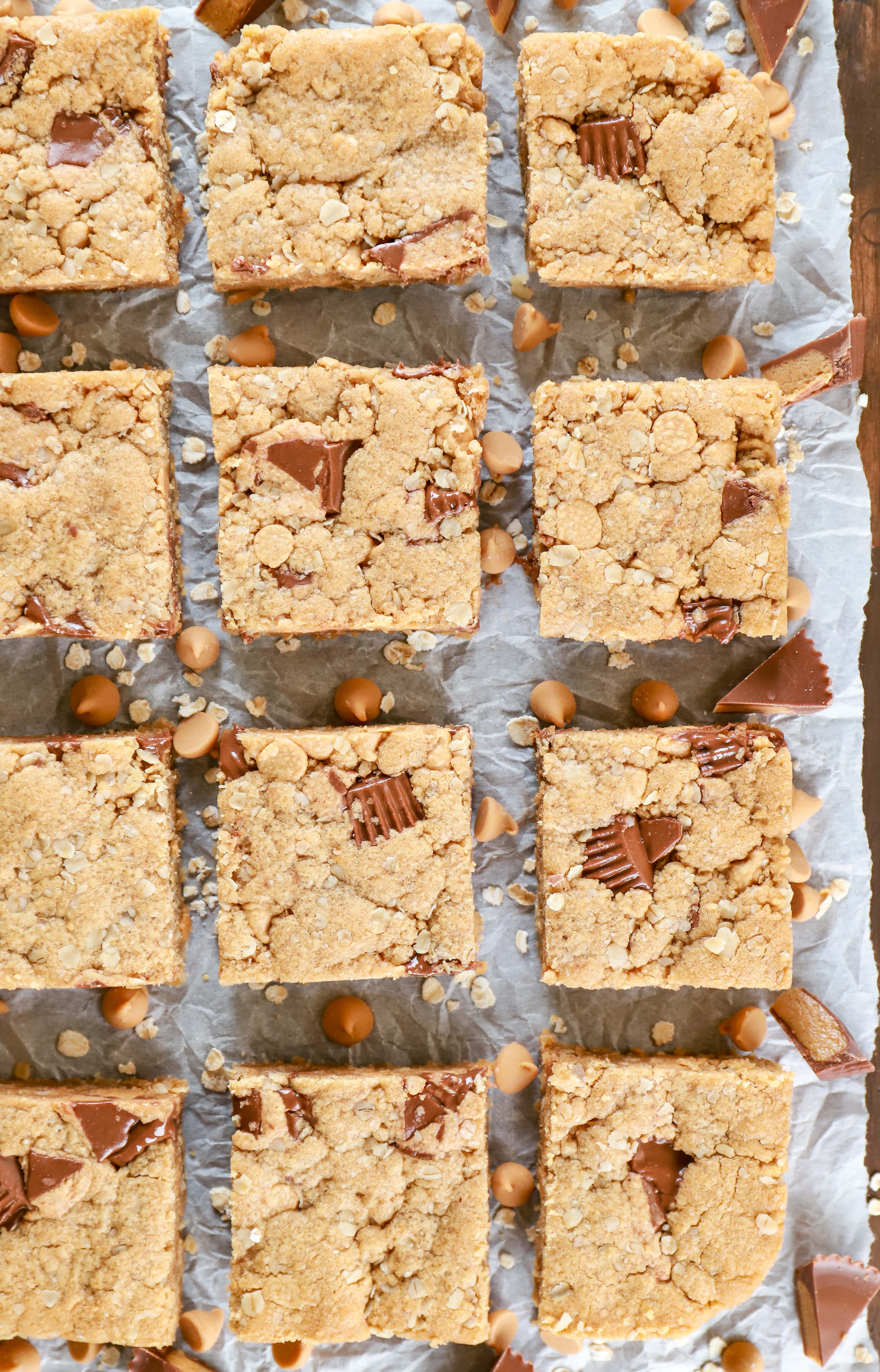 Overhead view of peanut butter overload cookie bars on parchment paper. Recipe from A Kitchen Addiction.