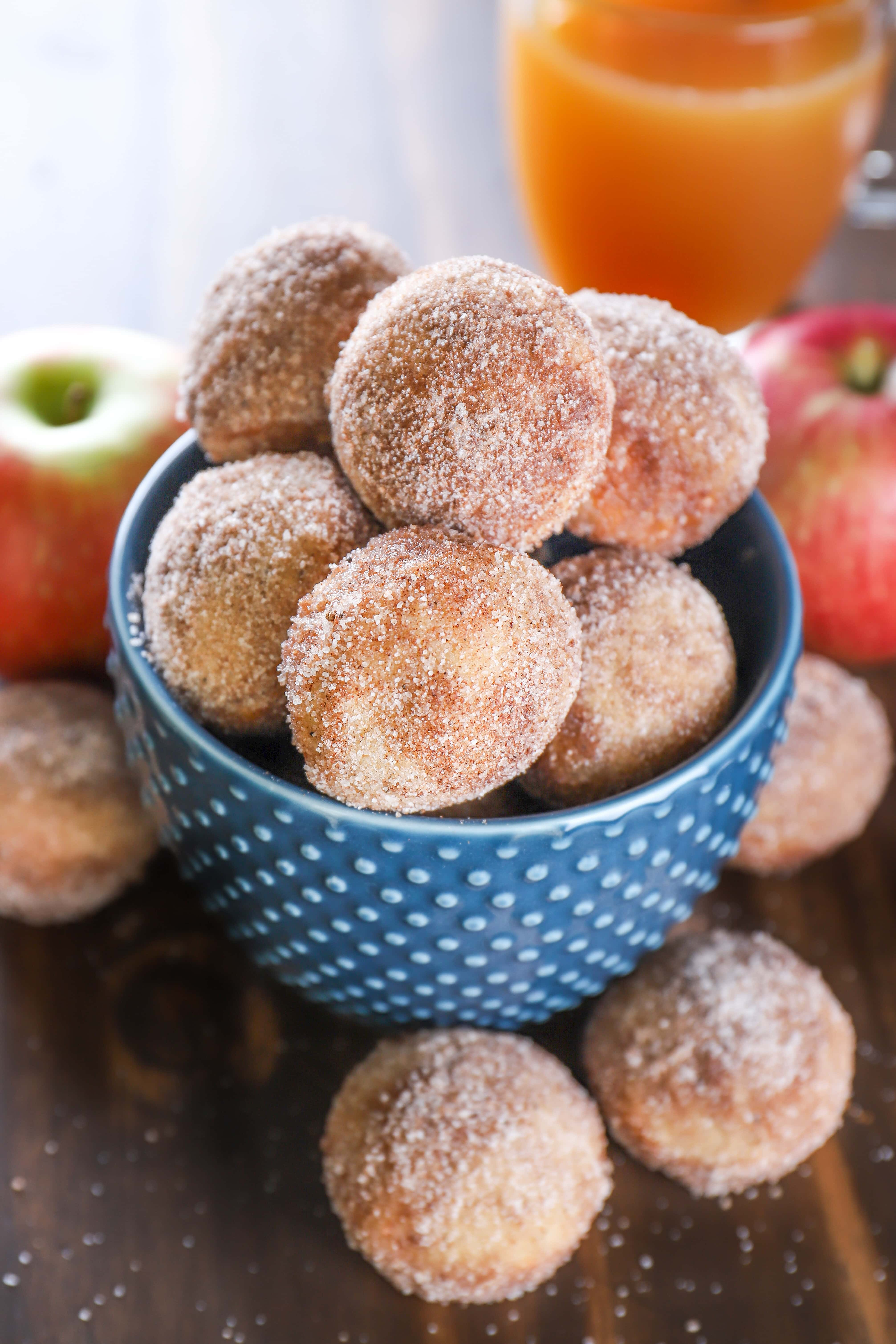 Bowl of Mini Spiced Apple Cider Donut Muffins with apples and a mug of apple cider. Recipe from A Kitchen Addiction