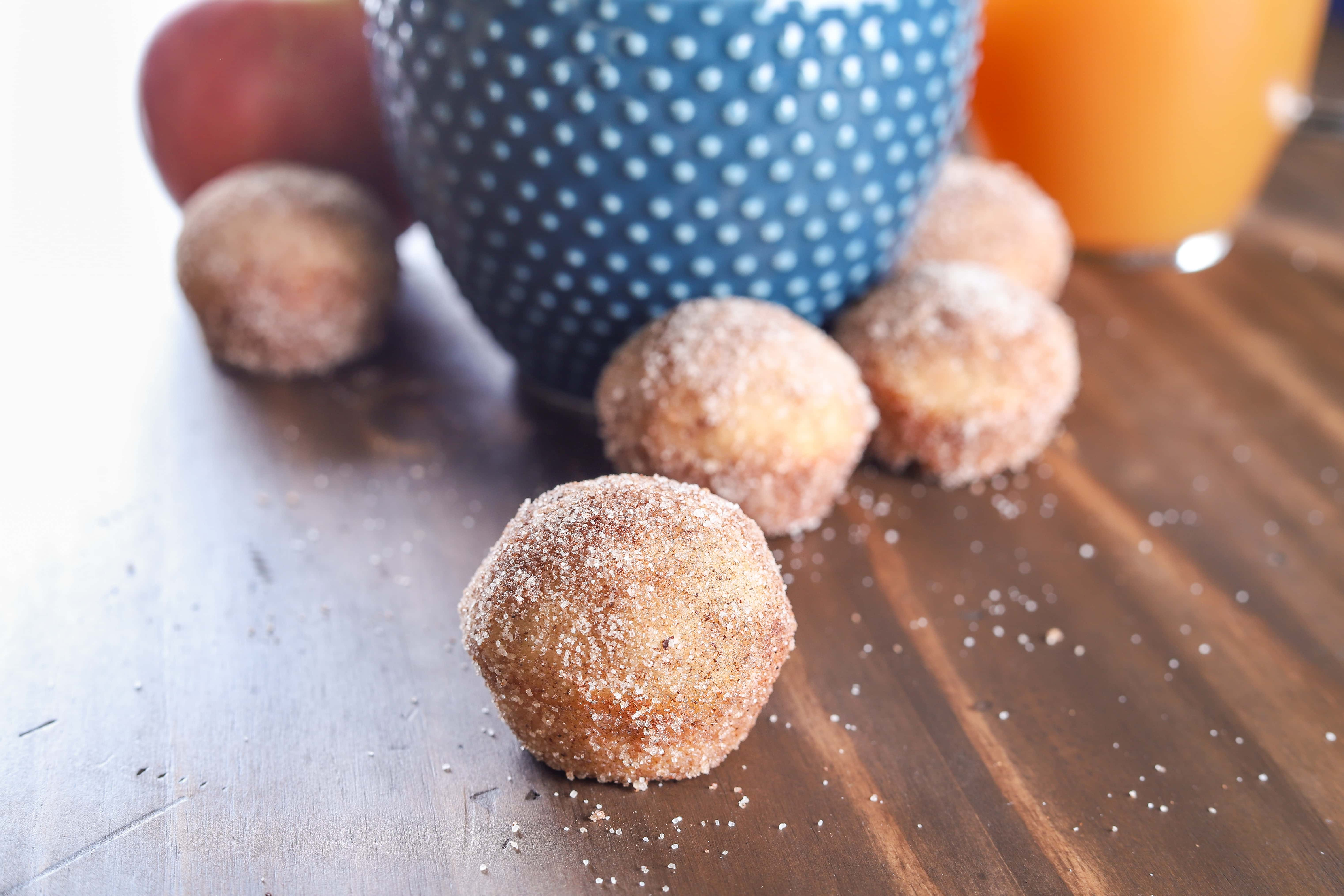 Spiced Apple Cider Mini Donut Muffins with a glass of apple cider. Recipe from A Kitchen Addiction