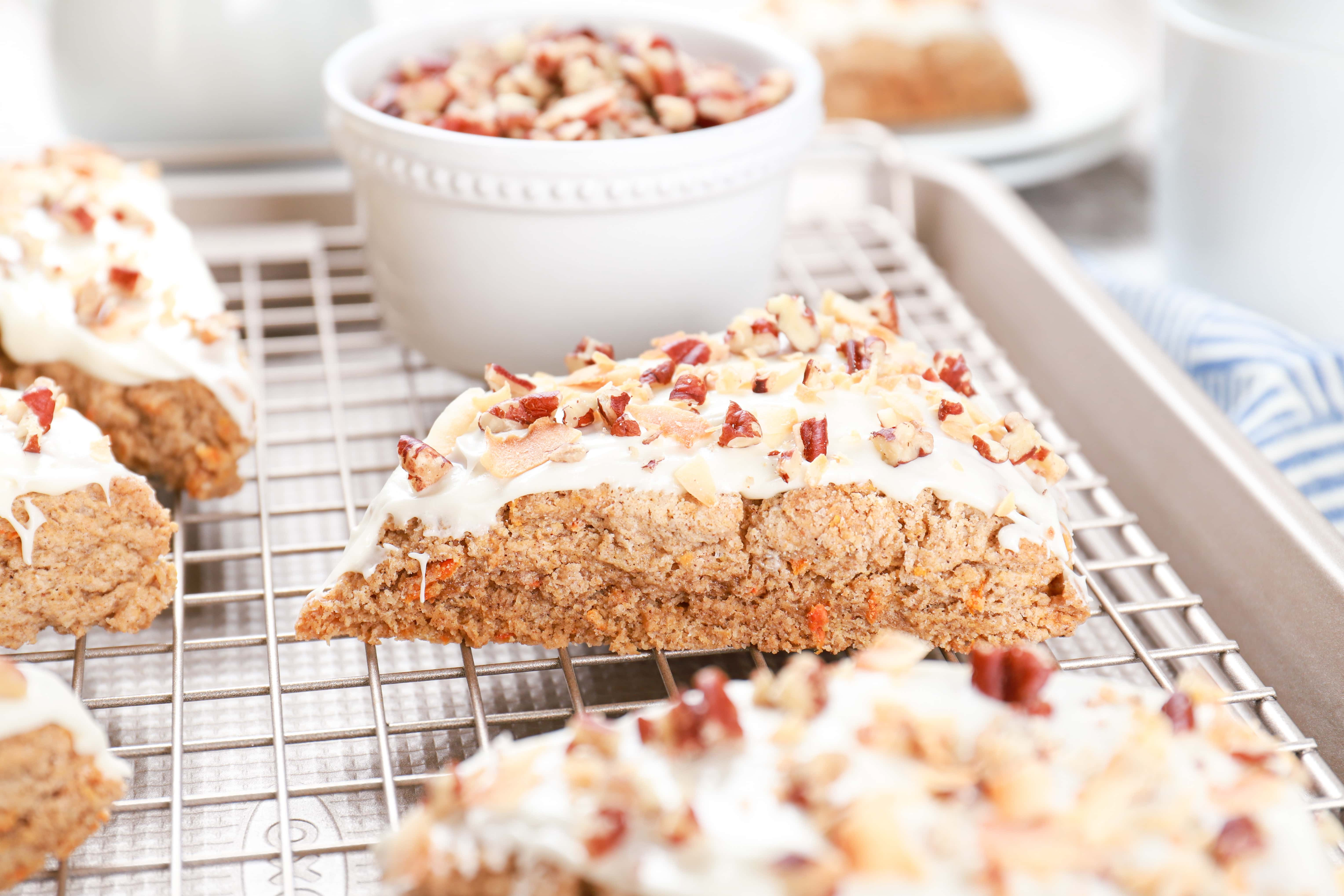 Carrot cake scone on a cooling rack with a bowl of chopped pecans in the background. Recipe for scones from A Kitchen Addiction