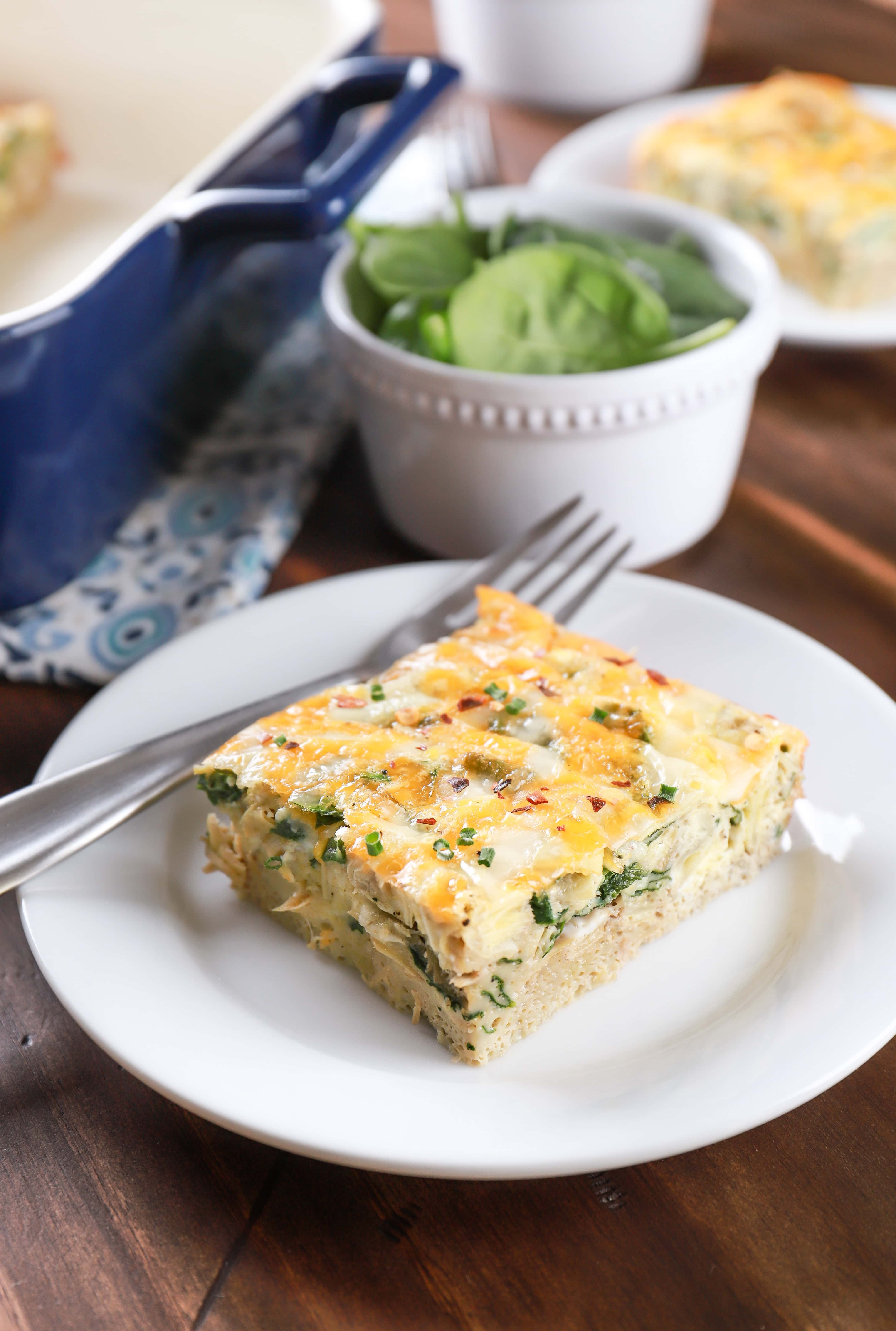 Two plates of cheesy spinach artichoke egg bake. Recipe from A Kitchen Addiction