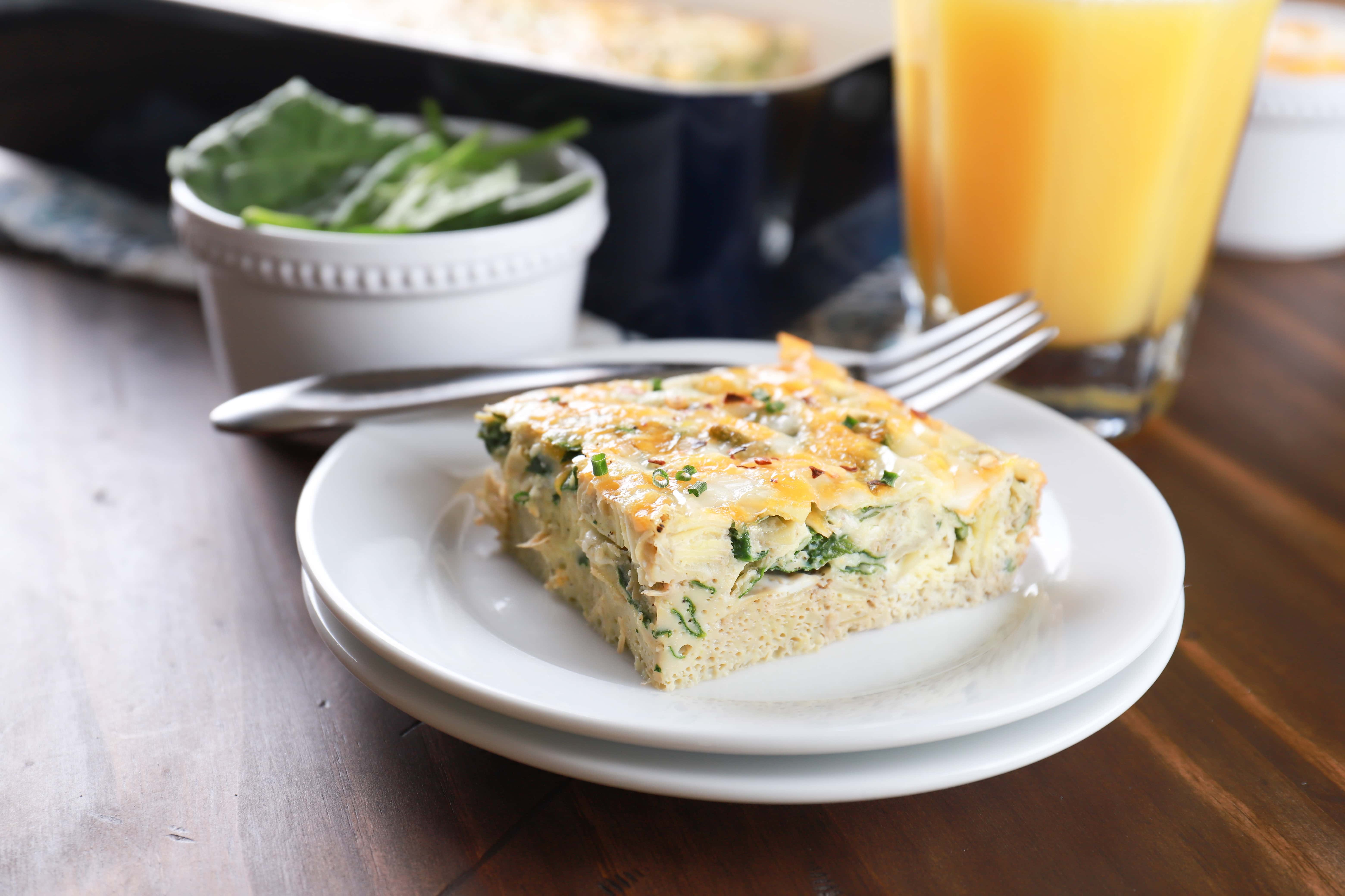 Piece of spinach artichoke egg bake on a white plate with a pan of egg bake in the background. Recipe for egg bake from A Kitchen Addiction