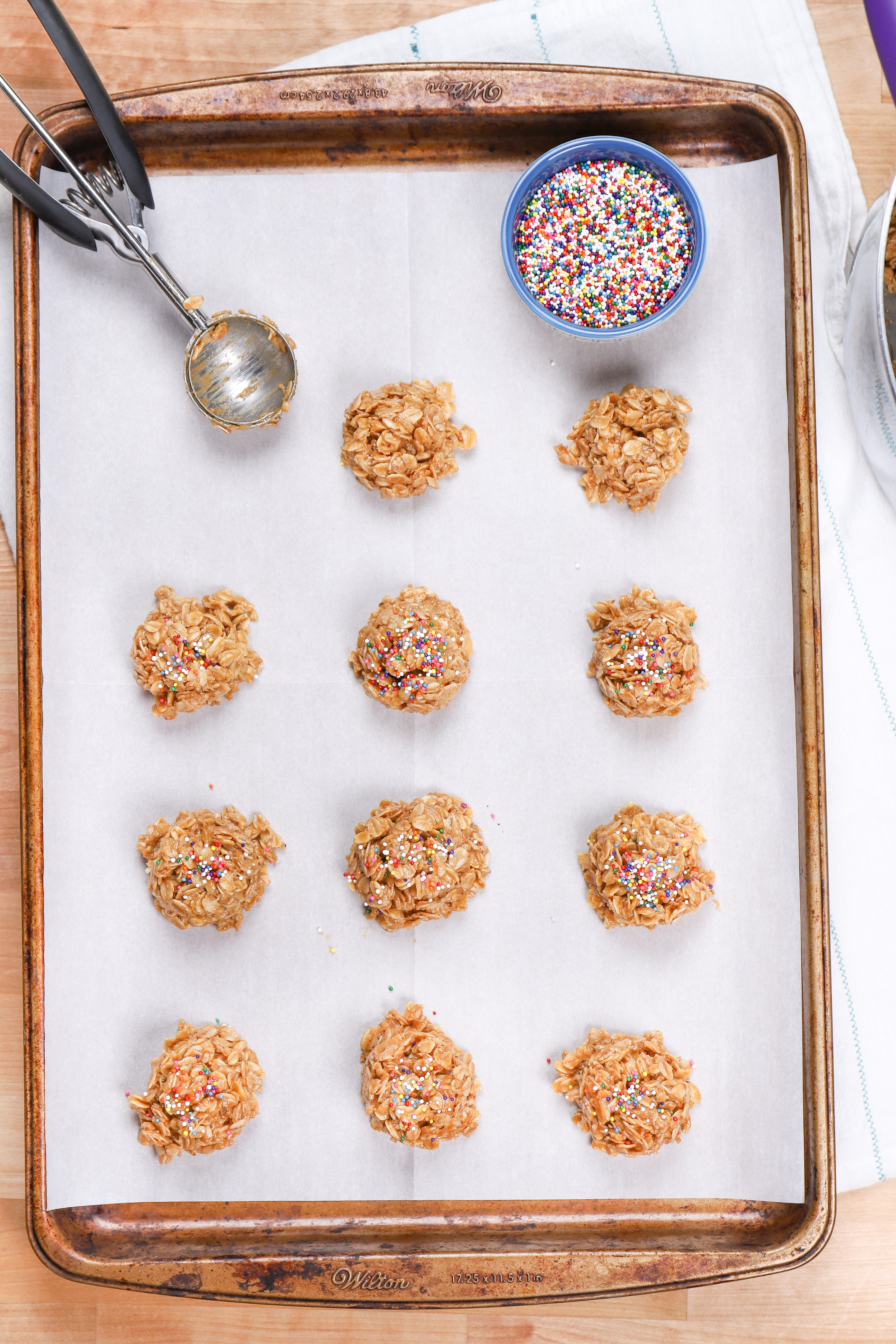 Putting peanut butter no bake cookies on a baking sheet with a cookie scoop