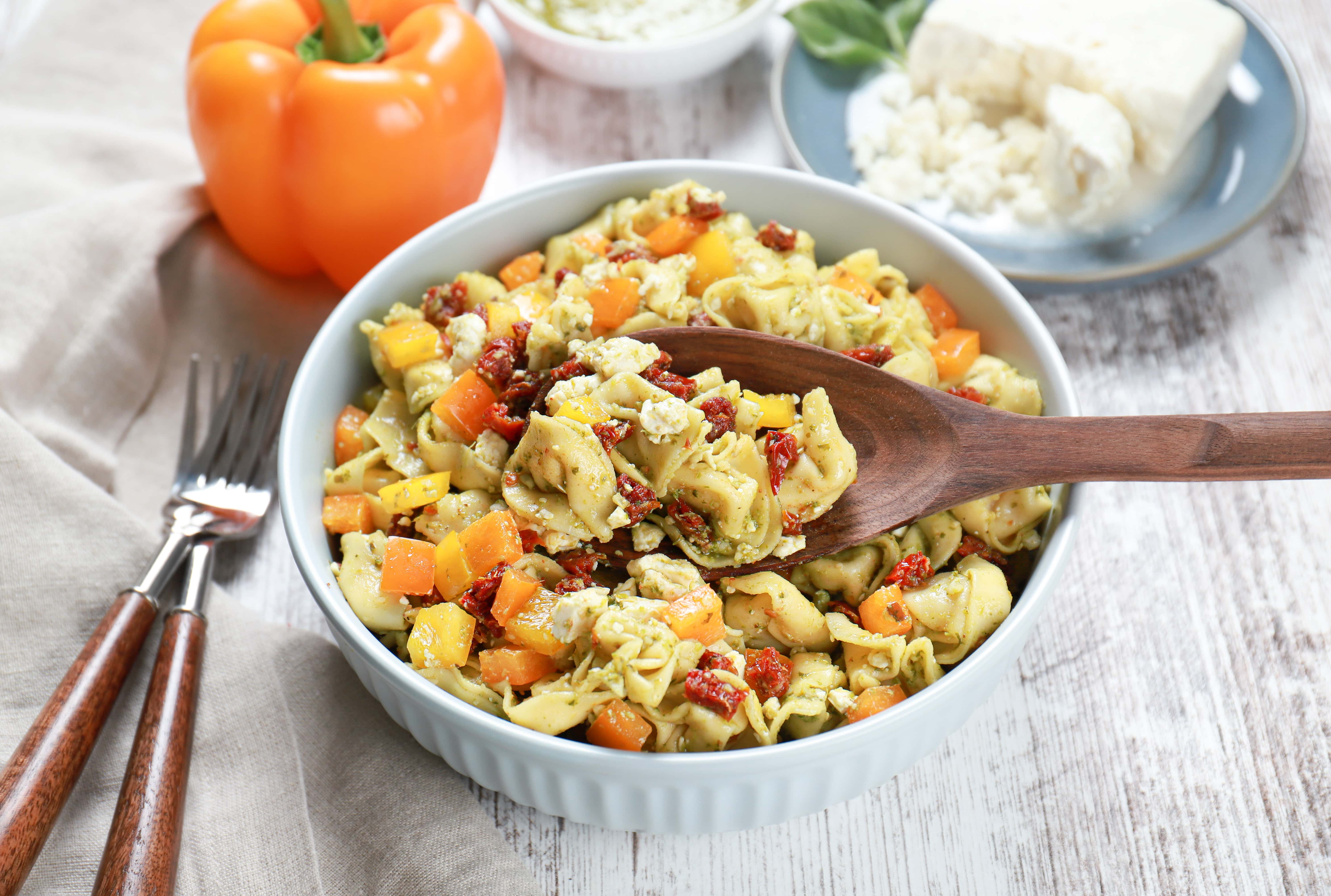 Above view of a wooden spoon full of pesto tortellini pasta salad.
