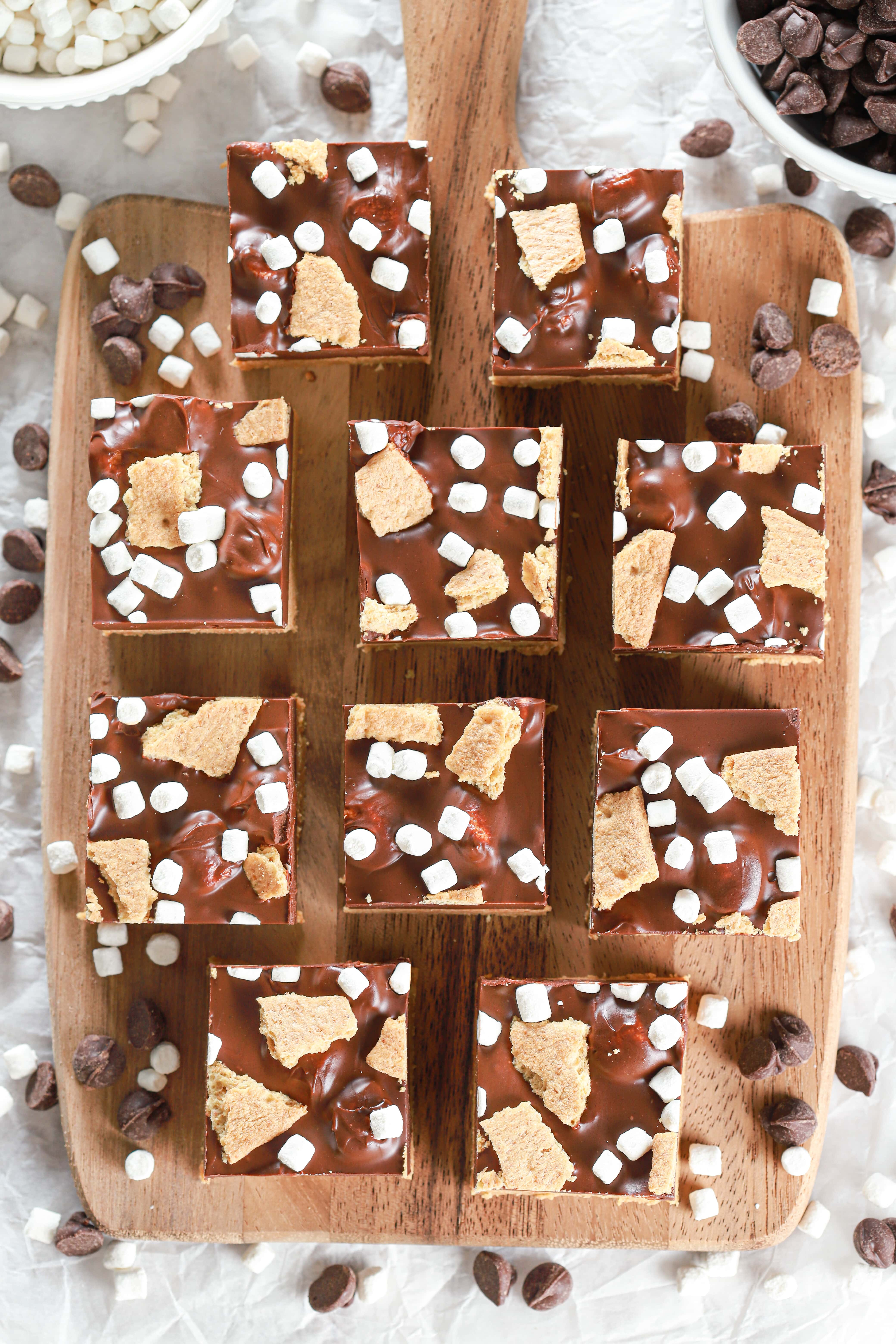 Overhead view of a batch of no bake peanut butter smores bars on a wooden cutting board.