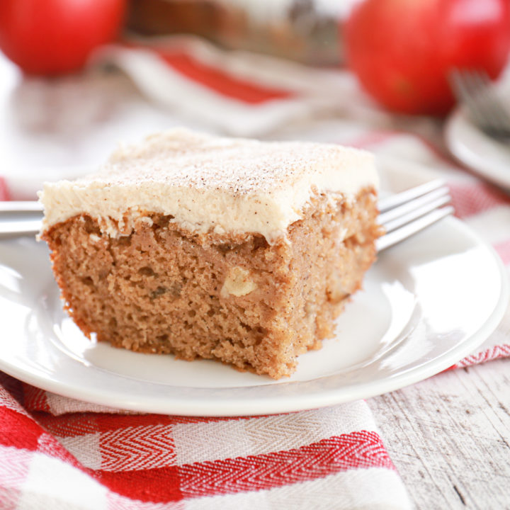 Up close view of a piece of apple cake on a small white plate with baking dish of remaining cake in the background.