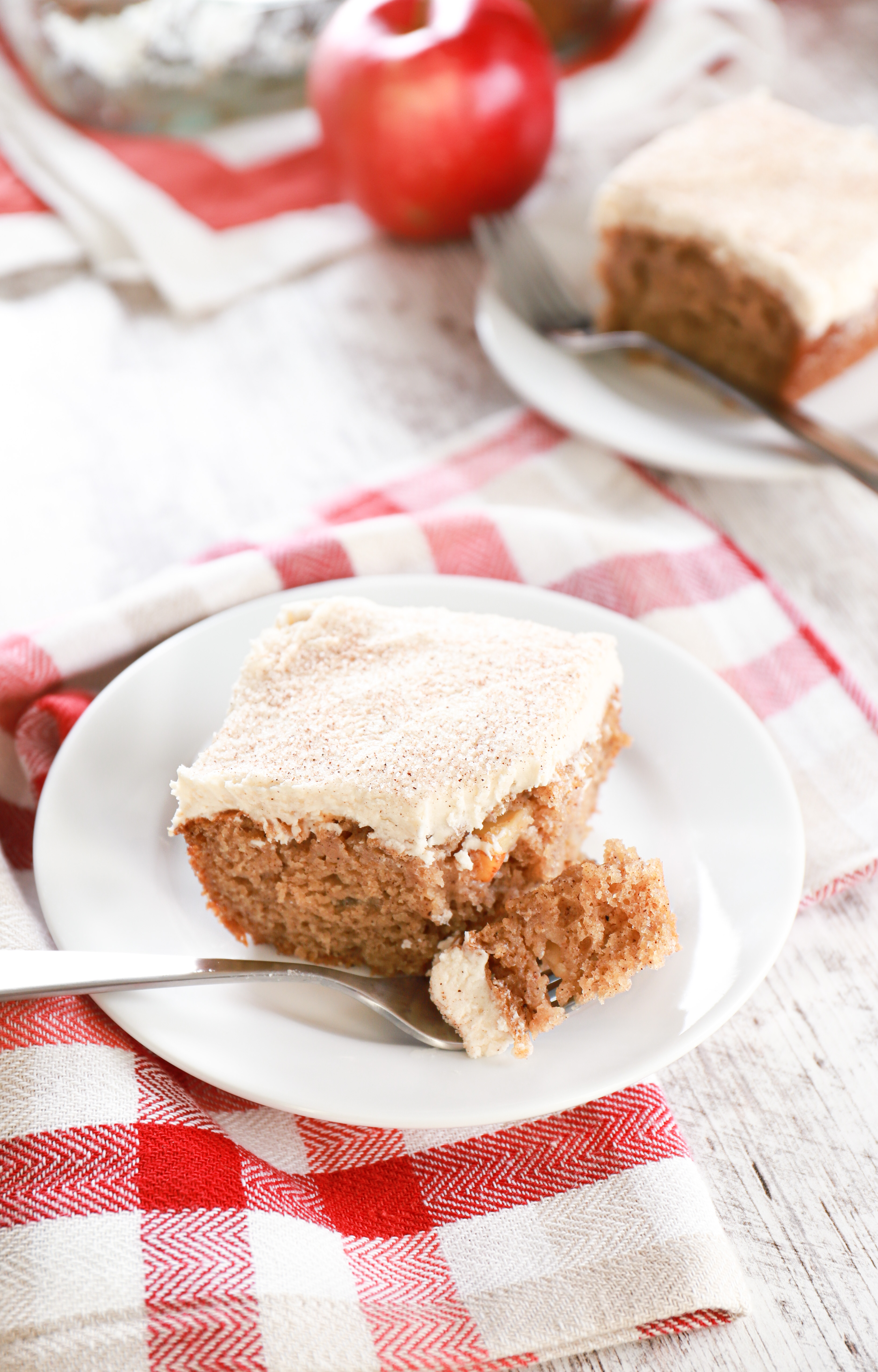 Piece of apple cake on a small white plate with a bite of cake on fork. Remaining cake in the background