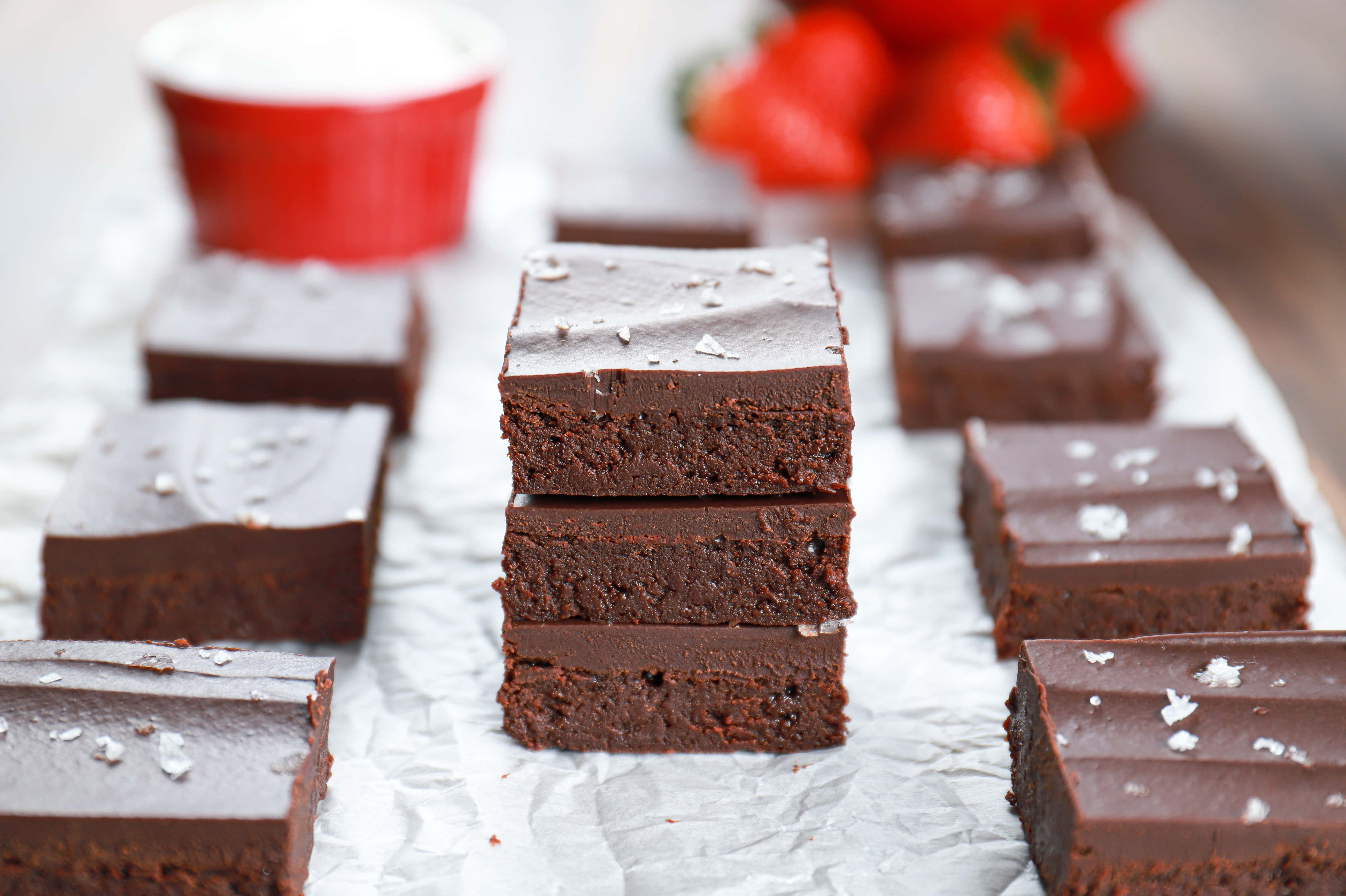 Three sea salt ganache topped flourless brownies stacked on a piece of parchment paper. Recipe from A Kitchen Addiction
