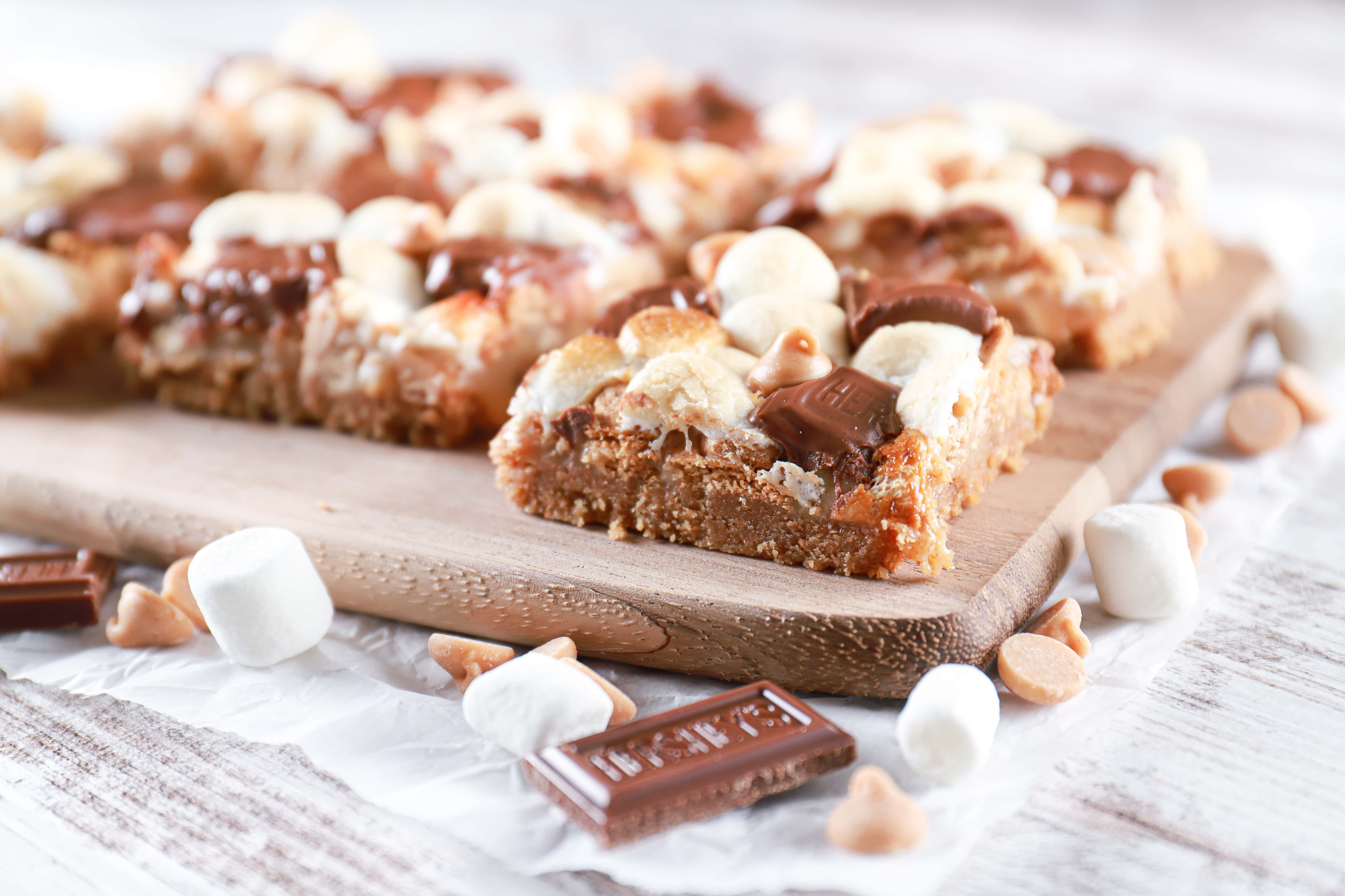 Peanut butter smores seven layer bars on a wooden cutting board. Recipe from A Kitchen Addiction