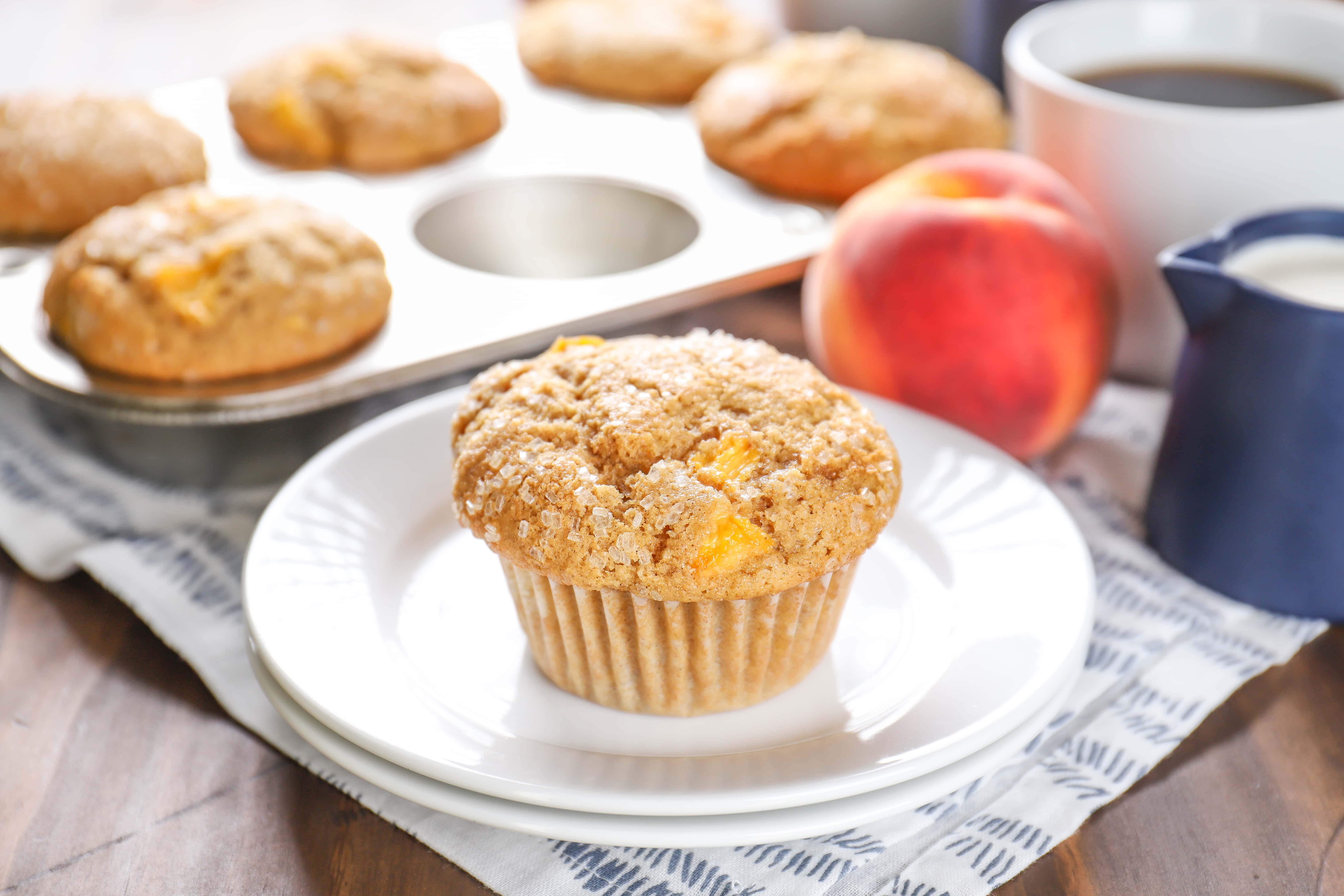 Peach Cardamom Muffins on a plate. Recipe from A Kitchen Addiction