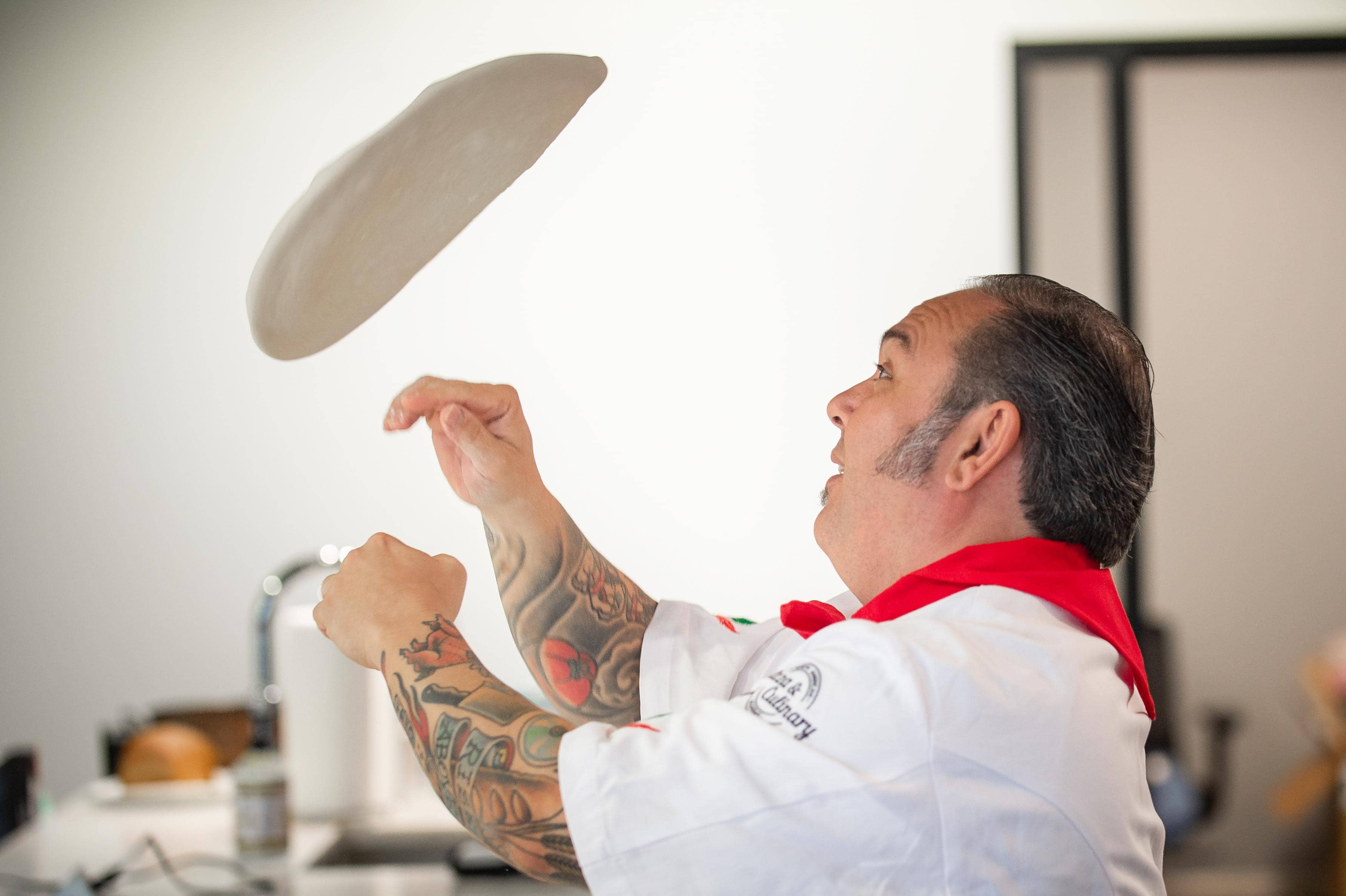 Chef Leo tossing pizza crust