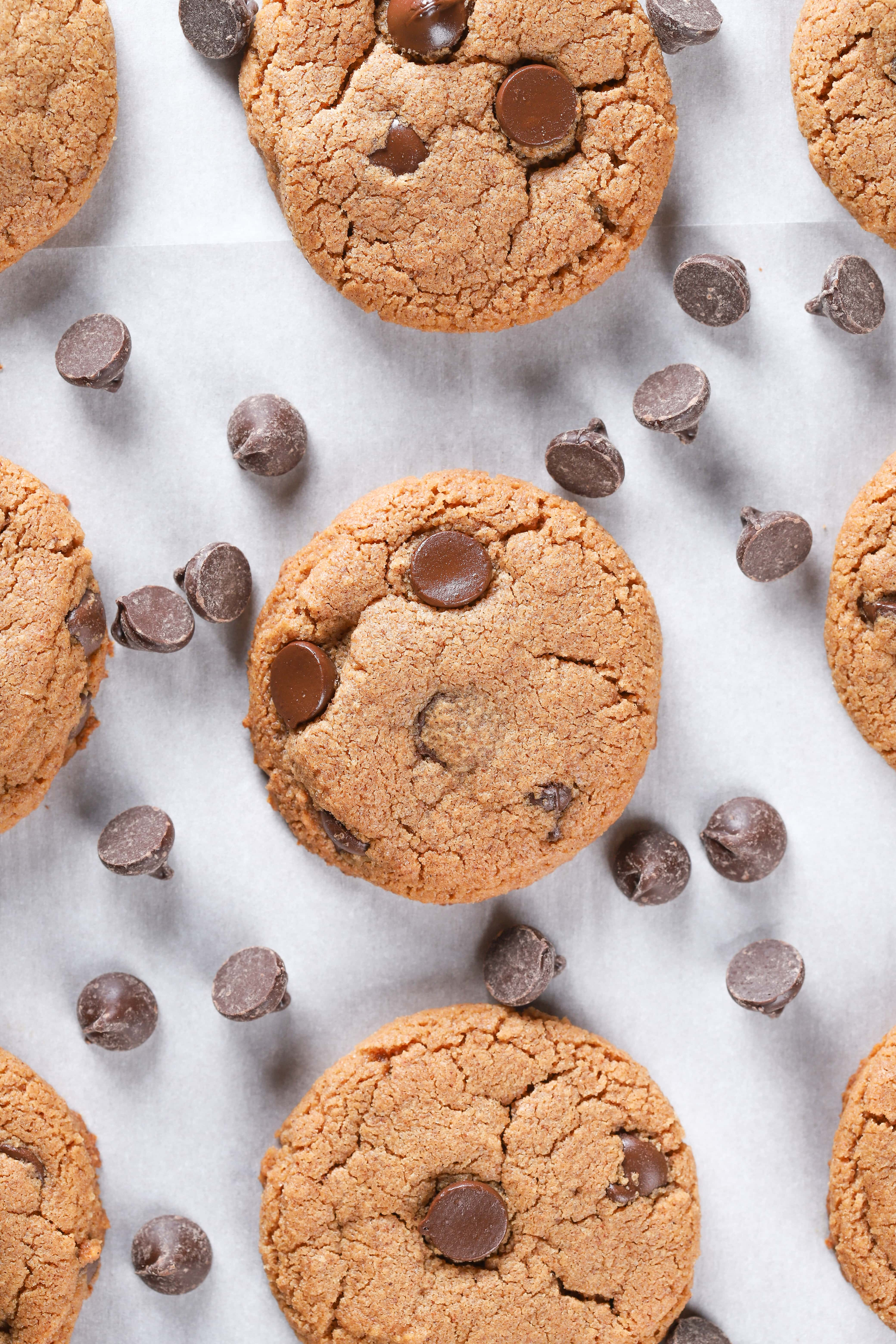Overhead view of a baking sheet full of flourless almond butter chocolate chip cookies. Recipe for cookies found on A Kitchen Addiction.