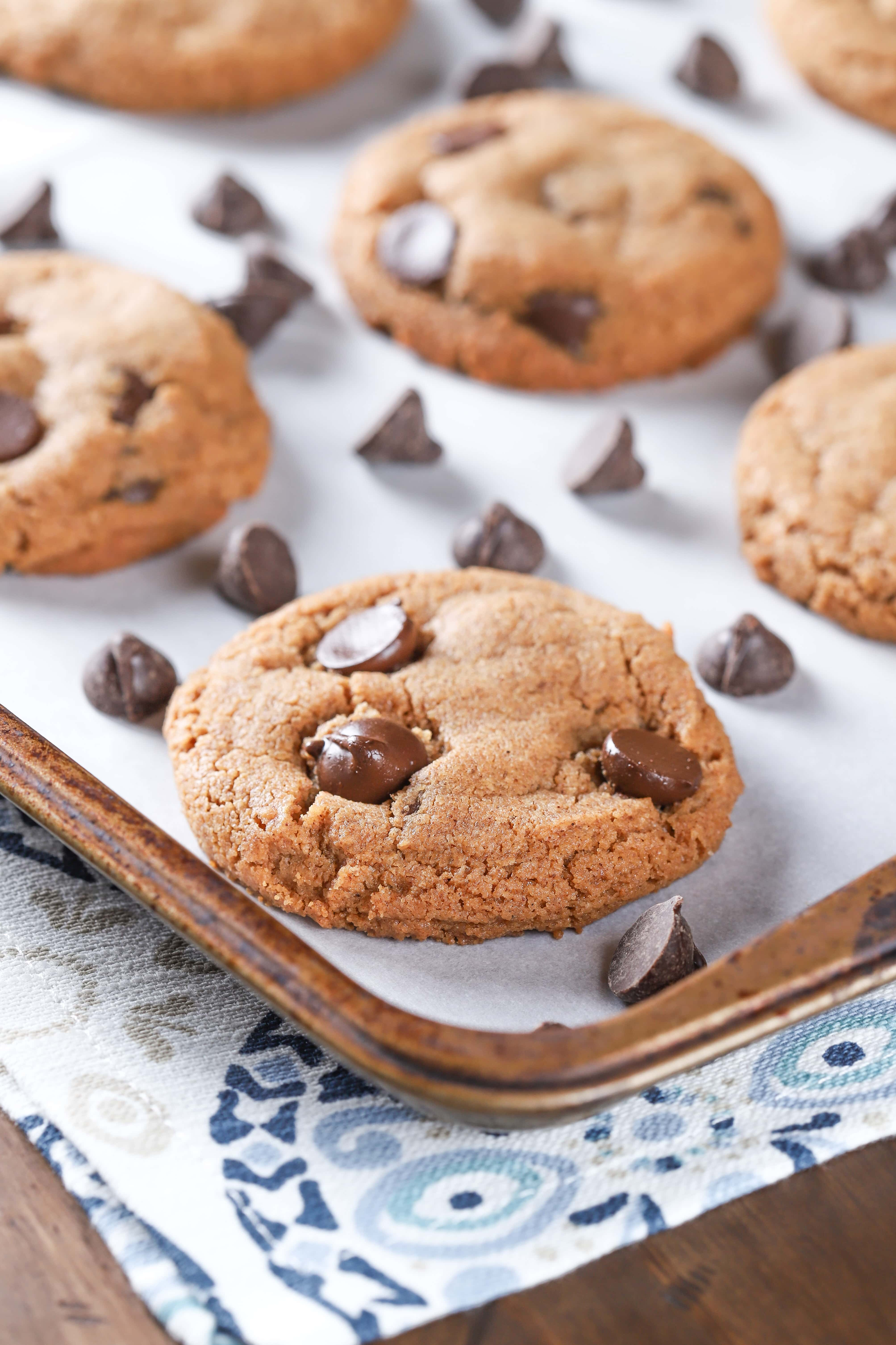 Up close image of a flourless almond butter chocolate chip cookie on a parchment paper covered cookie sheet. Recipe from A Kitchen Addiction