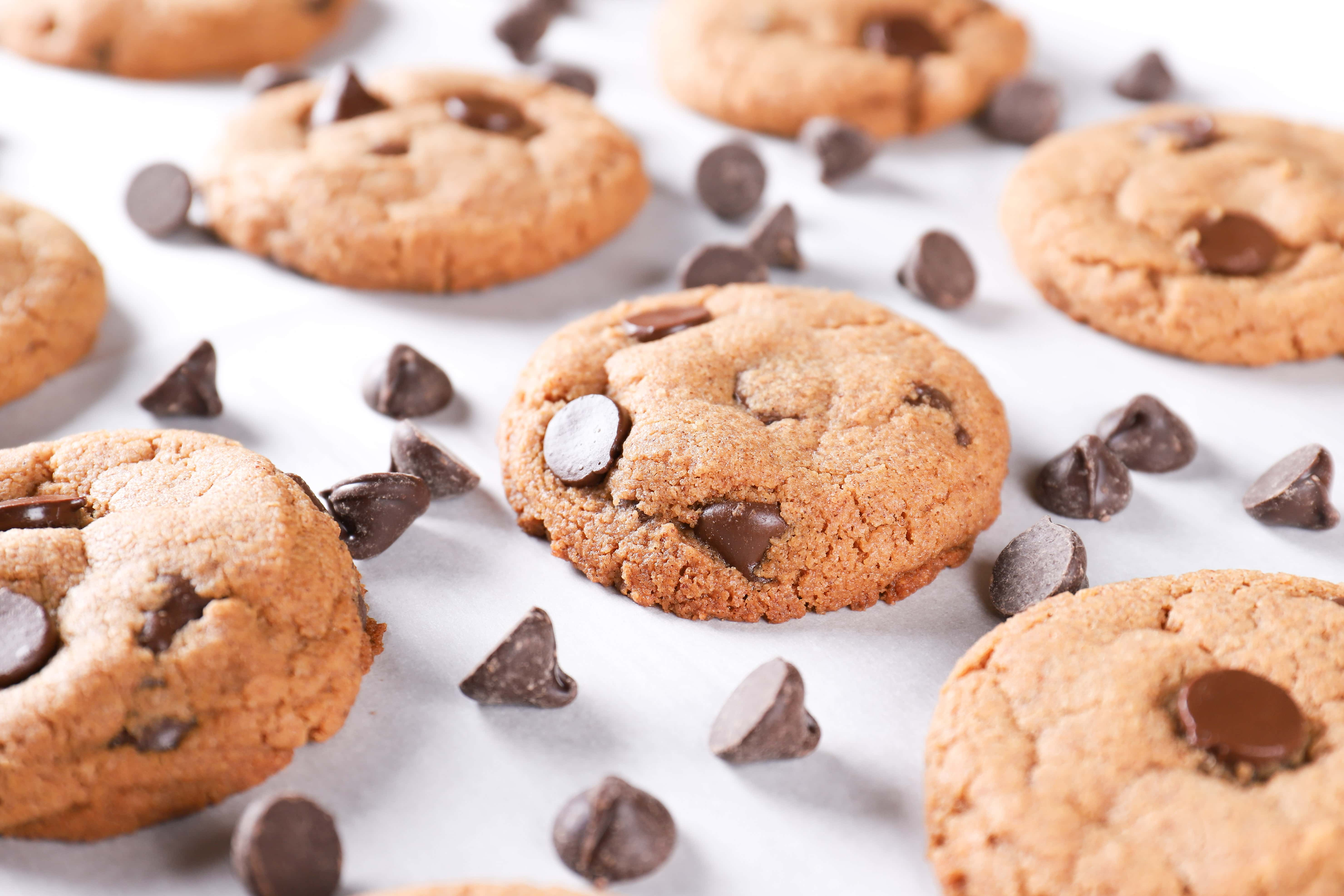 Side view of flourless almond butter chocolate chip cookies on a cookie sheet surrounded by chocolate chips. Recipe on A Kitchen Addiction