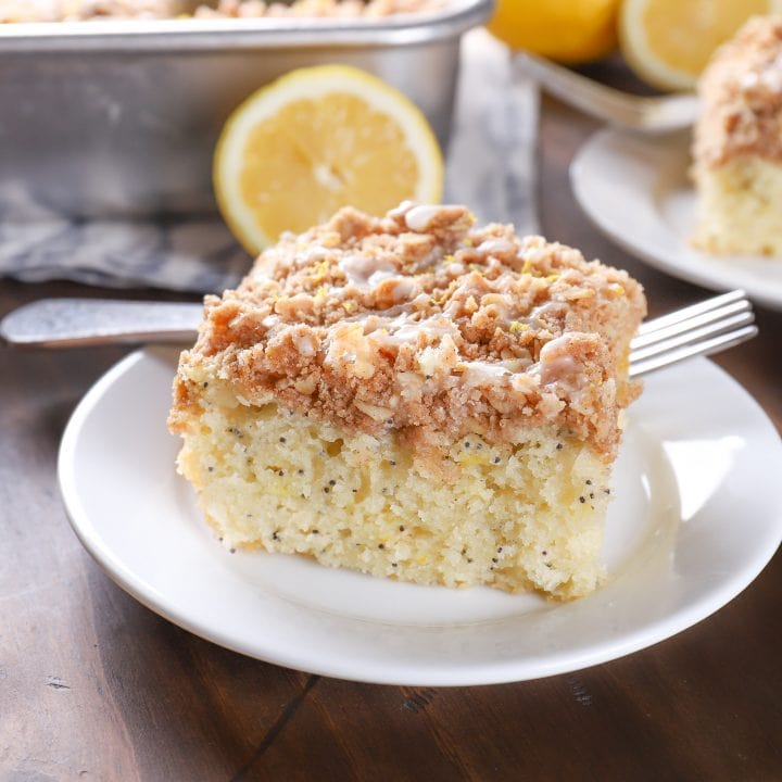 Up close image of a piece of lemon poppy seed cake on a white plate with a pan of cake in the background.