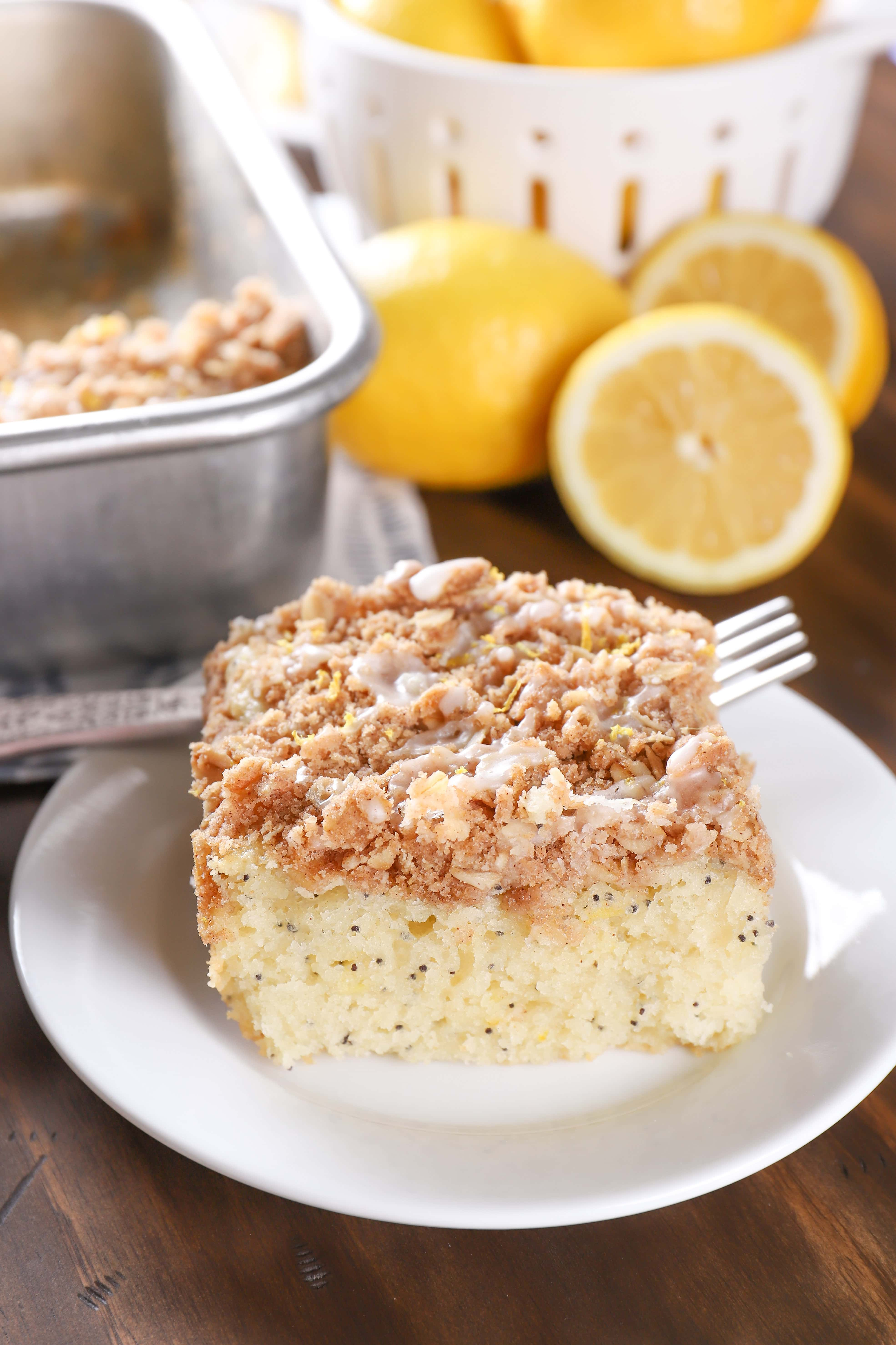 Piece of lemon poppy seed coffee cake on a white plate with lemons in the background. Recipe from A Kitchen Addiction