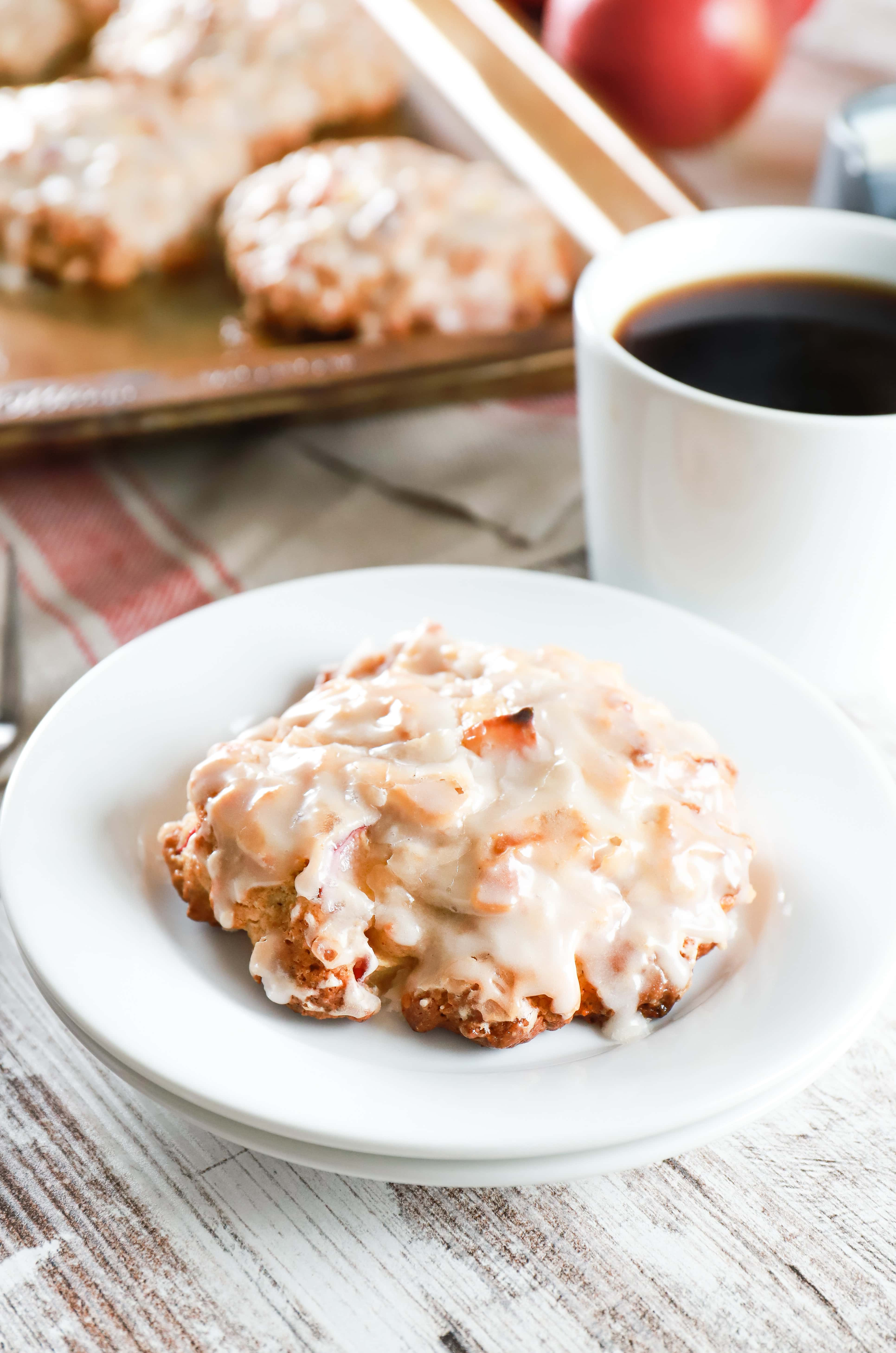 Baked apple fritter on a small white plate next to a cup of coffee. Recipe from A Kitchen Addiction
