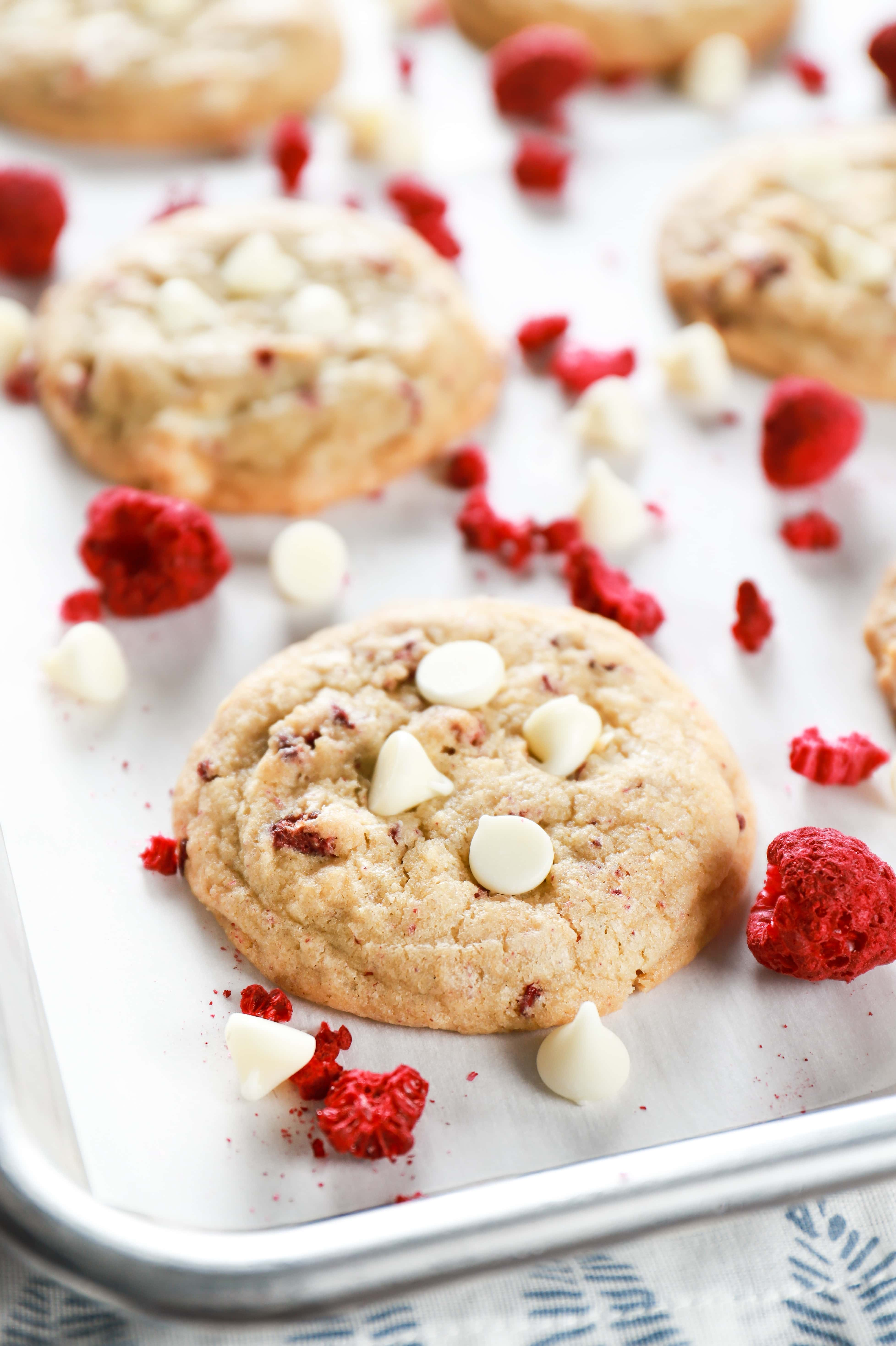 Up close image of a chewy white chocolate raspberry cookie on a parchment paper lined baking sheet. Recipe for cookies from A Kitchen Addiction