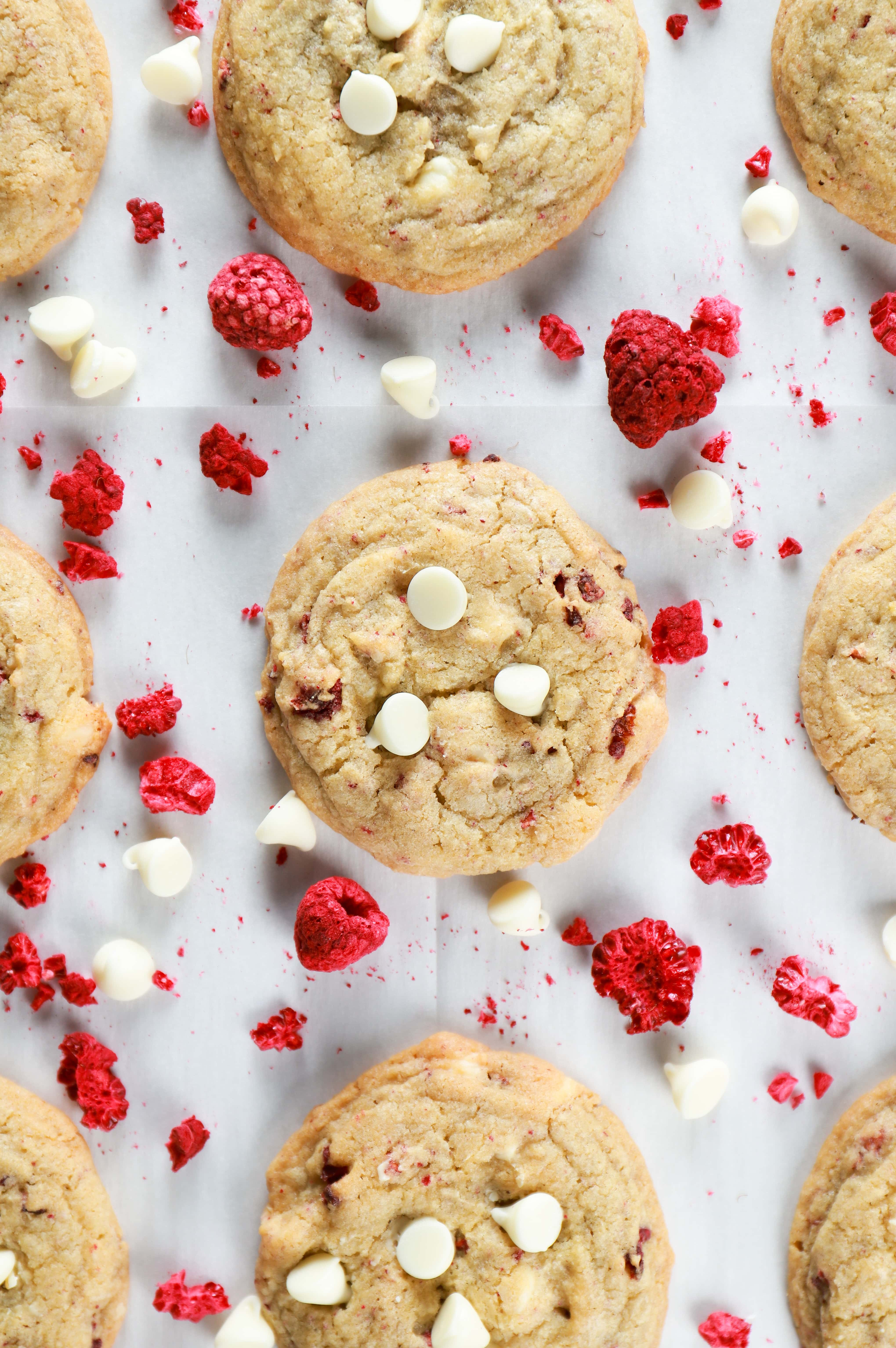 Overhead view of white chocolate raspberry cookies on a parchment paper lined cookie sheet. Recipe for cookies from A Kitchen Addiction