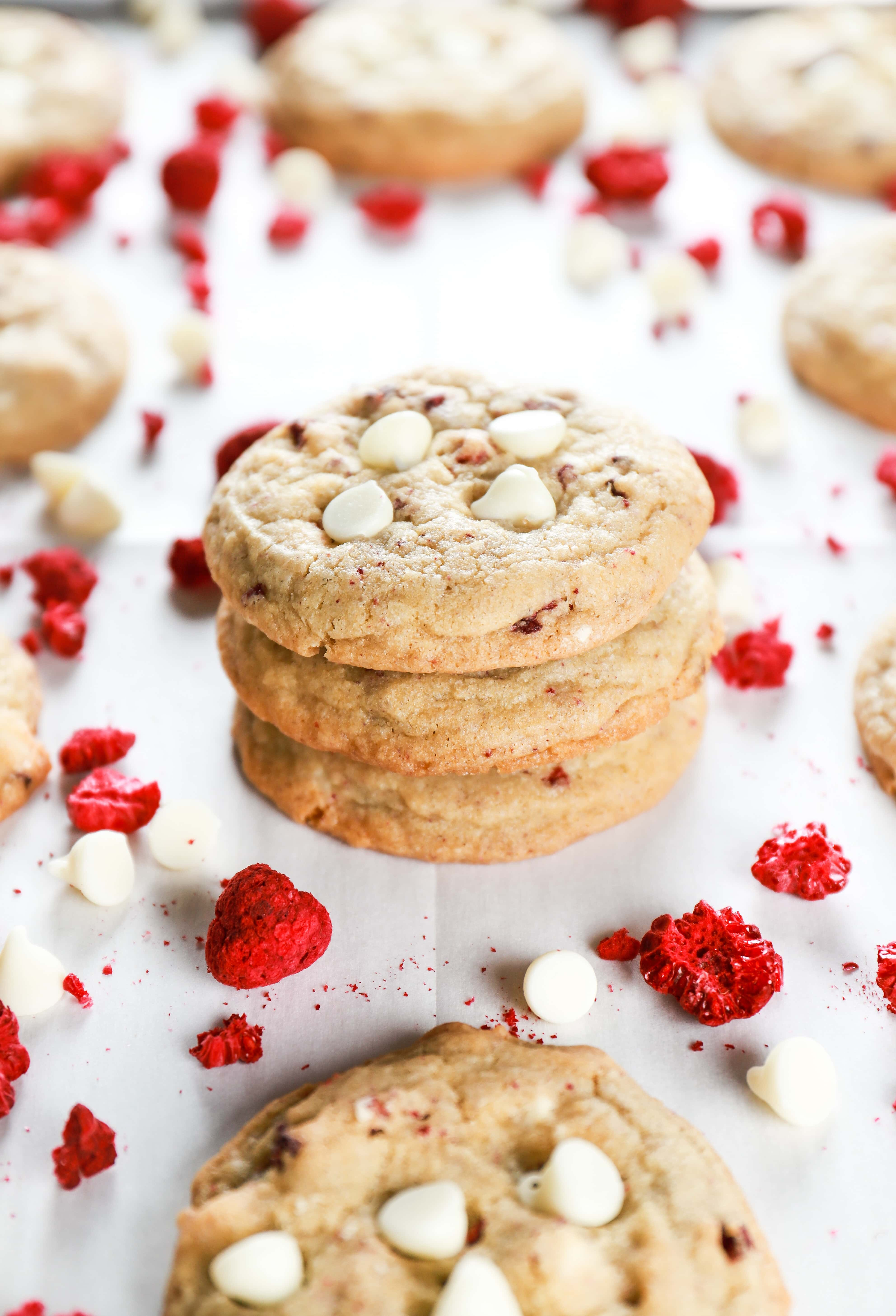 Stack of white chocolate raspberry cookies on a parchment paper lined cookie sheet. Recipe from A Kitchen Addiction
