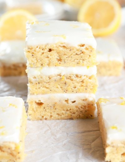 Stack of Glazed Lemon Poppy Seed Bars on parchment paper with more bars and lemons in the background. Recipe from A Kitchen Addiction