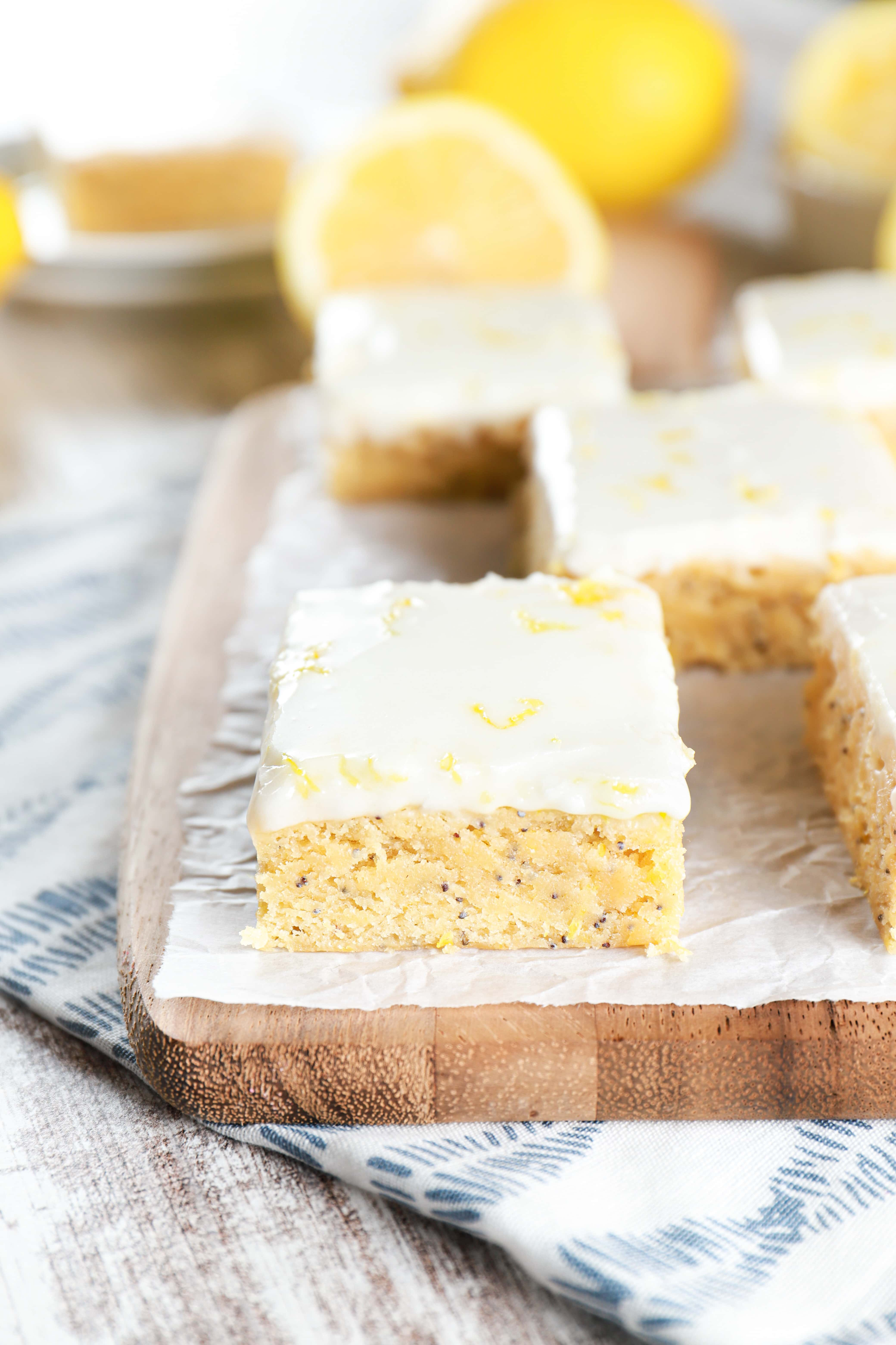 Up close image of glazed lemon poppy seed bars on a parchment paper lined cutting board. Recipe from A Kitchen Addiction
