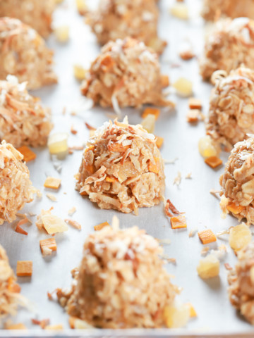 Tropical no bake cookies on a parchment paper lined baking sheet. Recipe for cookies from A Kitchen Addiction