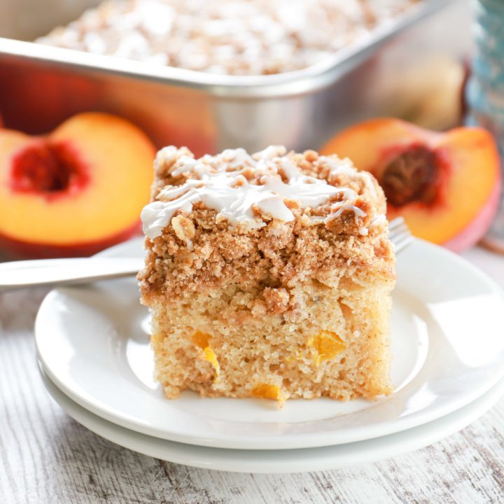 Up close side view of a piece of peach coffee cake on a small white plate.