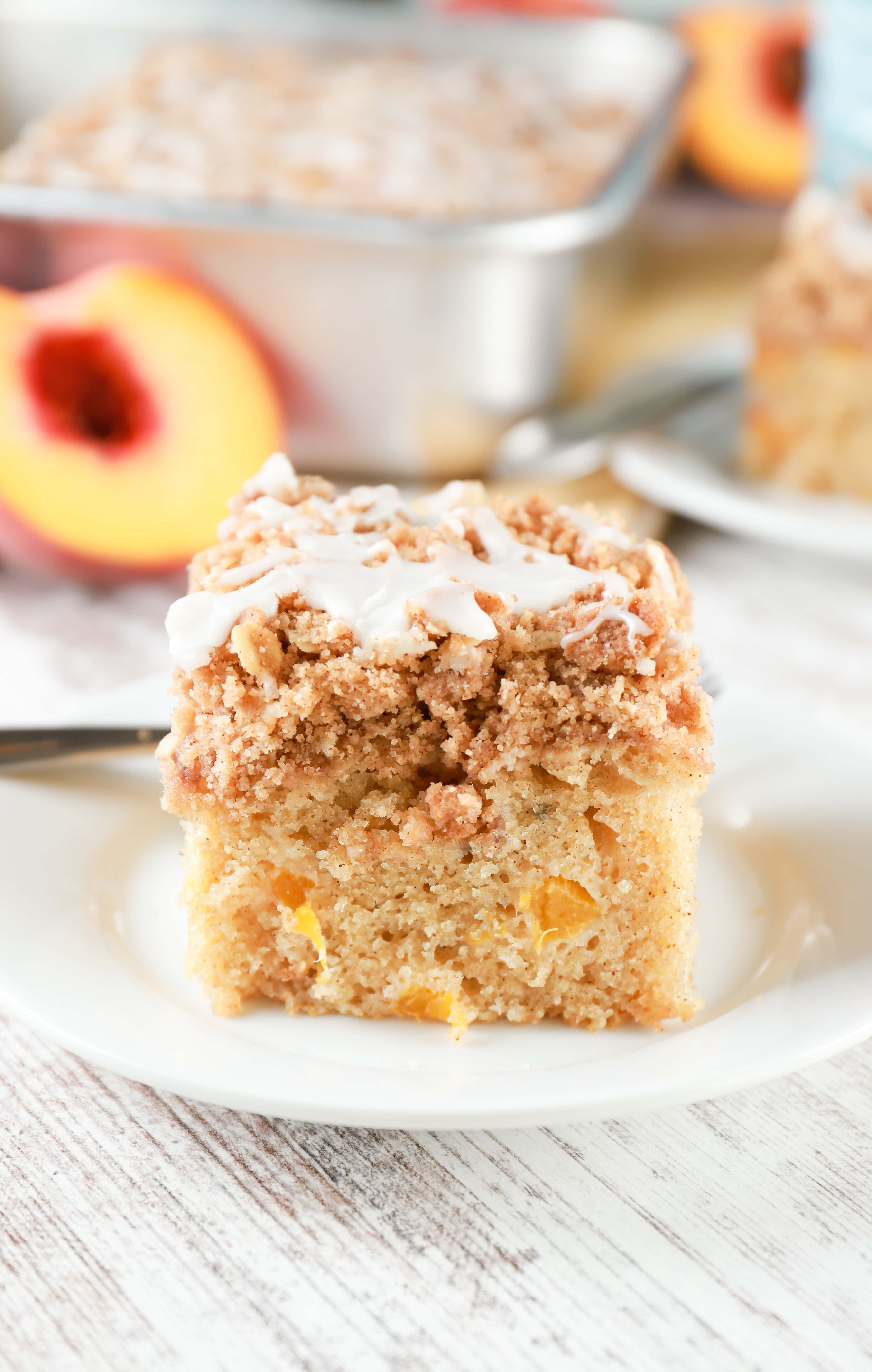 Side view of a piece of peach coffee cake with baking dish of peach coffee cake in the background.