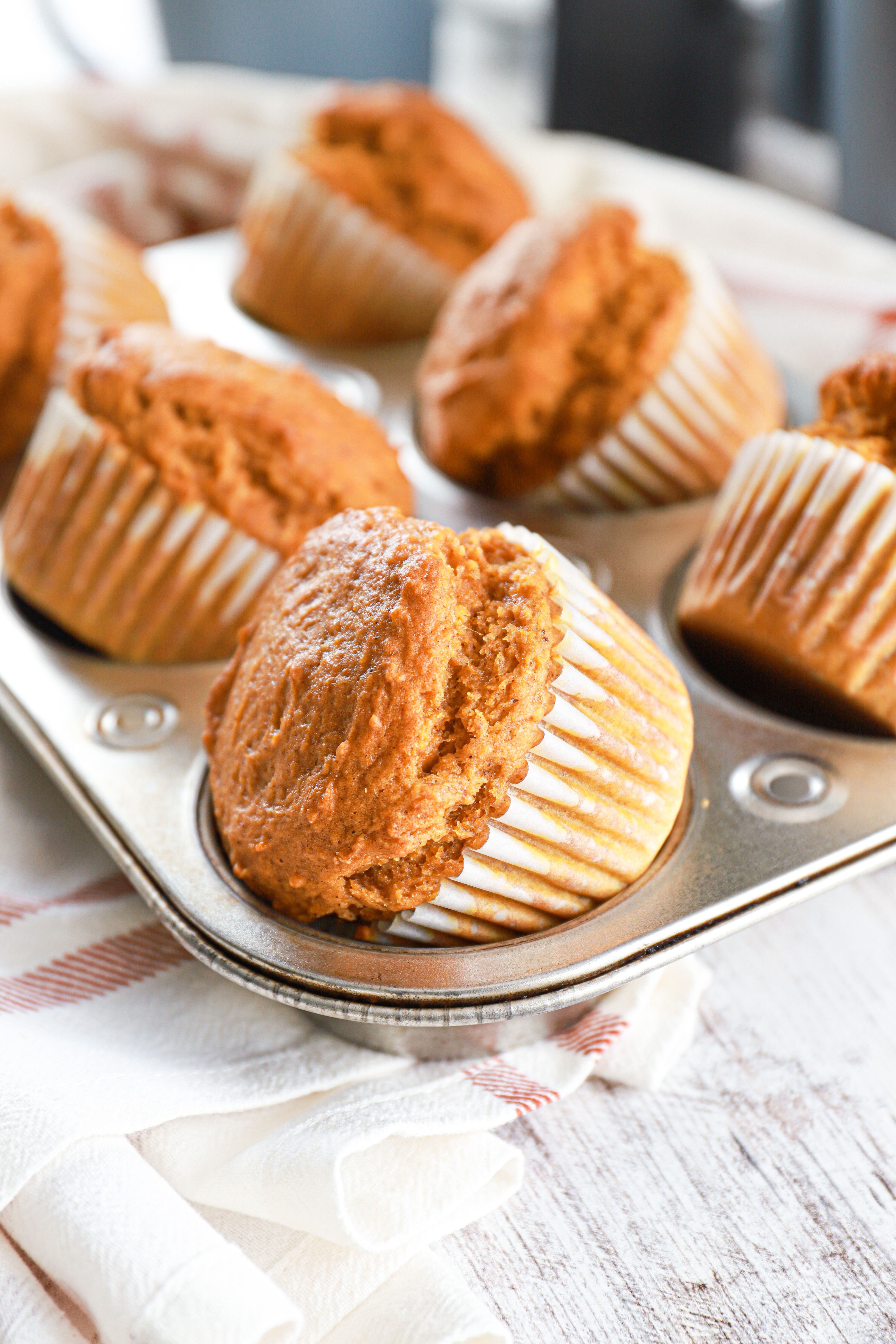 Side view of bakery style pumpkin muffins in a muffin tin